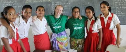 Students pose with school children during their volunteer teaching in Samoa.